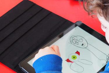 Photo d'un enfant dessinant sur une tablette